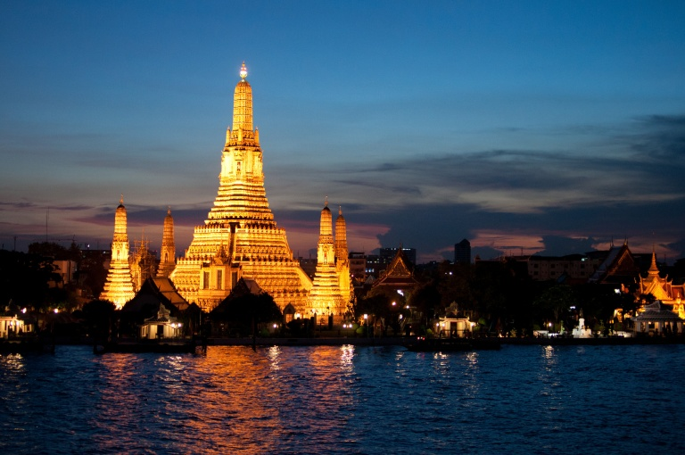 Wat Arun the Temple of the Dawn shines across the Chao Phraya River in Bangkok Thailand